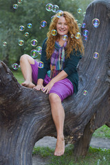 cheerful woman having fun with soap bubbles in park