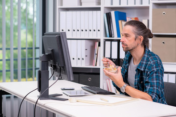 man is working in his officeand eating