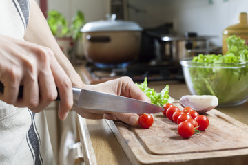 Woman cutting tomatoes to prepare meal at home