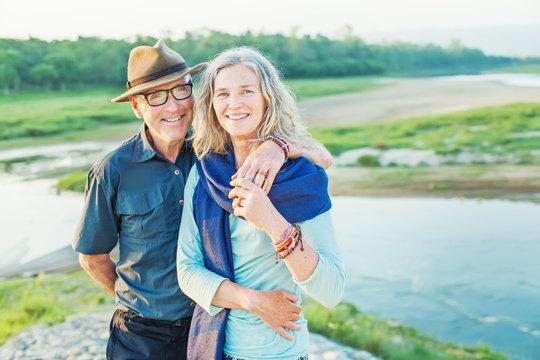 Beautiful senior couple standing in front of the river in autumn