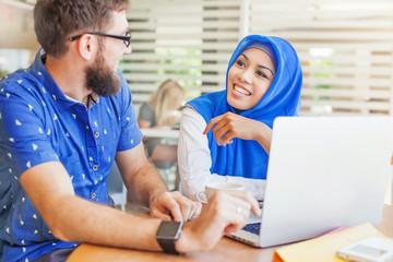 asian muslim woman and caucasian man looking at screen of laptop