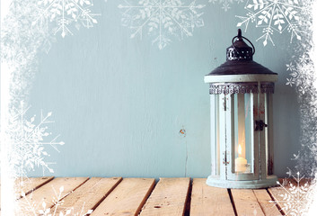 white wooden vintage lantern with burning candle and tree branches on wooden table. retro filtered image with snowflake overlay