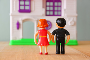 concept image of young couple in front of new house. little plastic toy dolls (male and female) , selective focus.