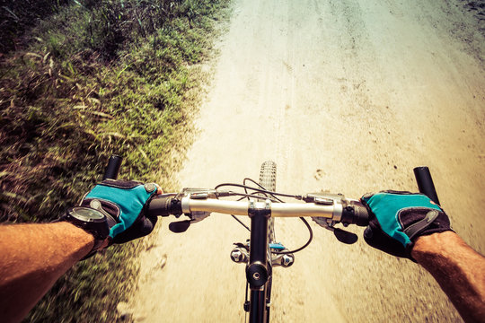 Closeup on hands and handlerbar of a man riding on a dirty road on a mountain bike