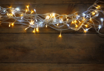 Christmas warm gold garland lights on wooden rustic background. filtered image