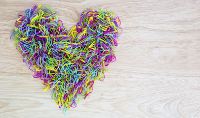 Colorful rubber band in heart shape on wood background