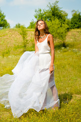 Beautiful girl in long white dress standing on summer meadow