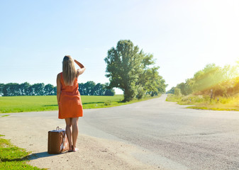 Young woman with suitcase looking at distance on country