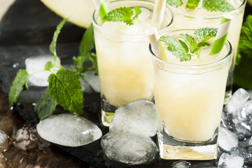 Fresh juice from the pulp of a melon, mint, ice and striped stra