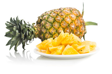 Fresh juicy nutritious cut pineapple with whole fruit as background