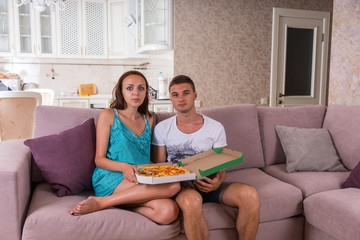 Young Couple Watching Television and Eating Pizza