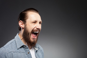 Cheerful young man with beard is expressing anger