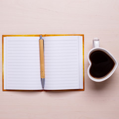 coffee cup in heart form and notebook