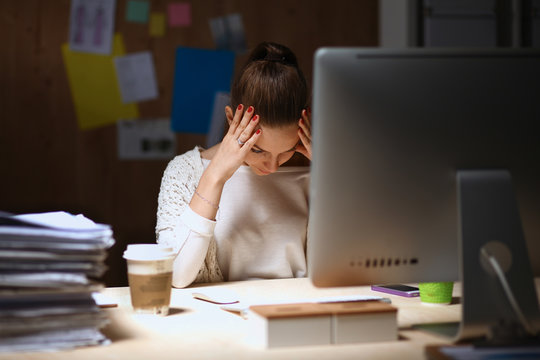 A portrait of a businesswoman staying late in the office with a
