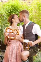 Glückliches bayrisches Paar in Tracht mit Bier und Brezn