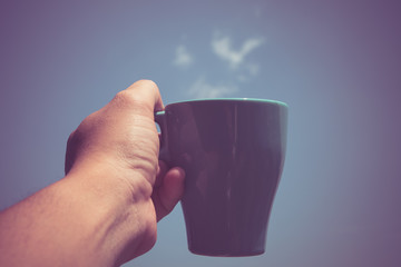 man holding coffee cup in his hand in front of blue sky