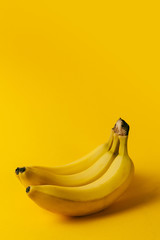 Ripe bananas on the yellow background