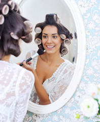 Beautiful woman in hair curlers puts on morning makeup with powder brush