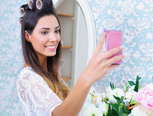 Beautiful woman with hair curlers taking photo of herself with a phone