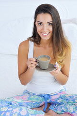 Portrait of a smiling beautiful woman sitting in bed with a cup of morning coffee with cream