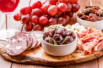 Wine snack set. Variety of cheese and meat on dark background.
