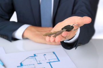 Real-estate agent giving  a house  key. The plan of a flat behin
