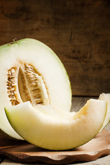 cut melon and slices on a wooden table, selective focus