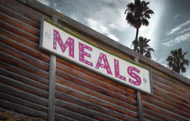 aged and worn vintage photo of meals sign with palm trees