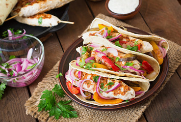 Mexican tacos with chicken, grilled vegetables and red onion.