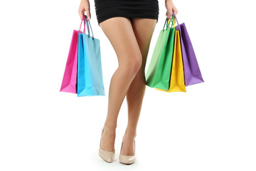 Female legs in beige high-heeled shoes with shopping bags on whi