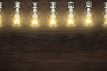 glowing bulbs over wooden background