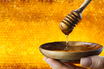 Honey dripping on honeycombs background