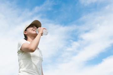 ペットボトルで水分補給をする女性