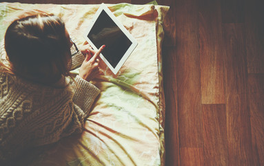 Woman lying in bed with digital tablet touching with finger. Vie