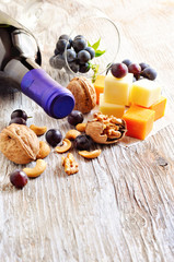 Bottle of red wine, cheese, walnuts, cashews and grapes. Toned image, selective focus