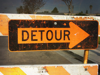 aged and worn vintage photo of detour sign with arrow