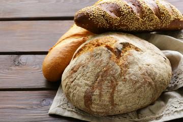 homemade fresh bread (rye, sesame, white) on a wooden background
