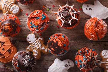 Halloween cupcakes and gingerbread cookies closeup. horizontal top view
