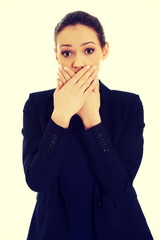 Excited young business woman covering her mouth.