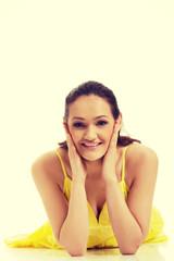 Beautiful woman lying in yellow dress.