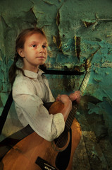 child playing guitar in grunge ruined room