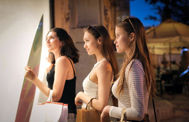 Three girls looking at the window of a shop