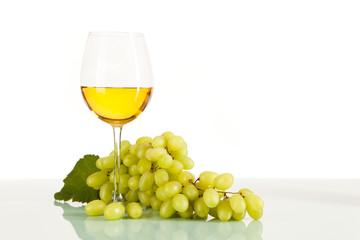 Weißwein im Glas umgeben von grünen Weintrauben