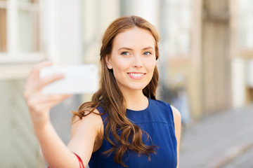 happy woman taking selfie with smartphone in city