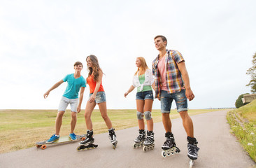 happy teenagers with rollerblades and longboards
