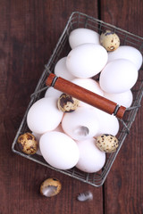 white chicken and brown quail eggs in a basket
