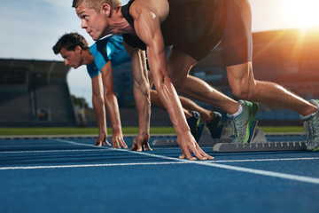 Fit athlete running race in athletics racetrack on a sunny day Wall mural
