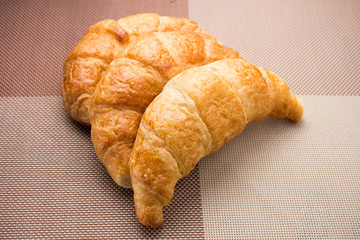 Croissant three pieces arranged on a brown cloth.