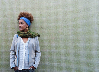 Headshot of young afro american curly woman in front of tiled ba