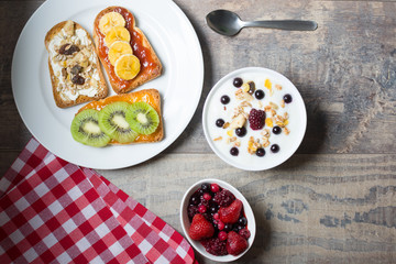 Natural yogurt with fresh berries, toast with fruit and cereals